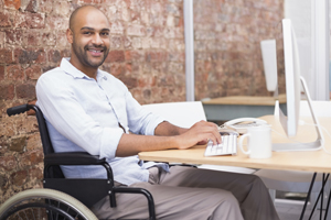 smiling-businessman-in-wheelchair-working-at-his-desk-gm516651699-48388598-300x200.jpg