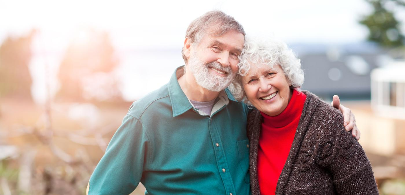 Senior couple holding each other smiling